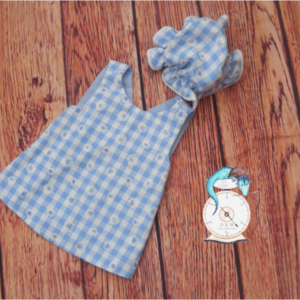 Blue pinafore and mop cap. 10% of all sales goes to breast cancer and honeybee research.