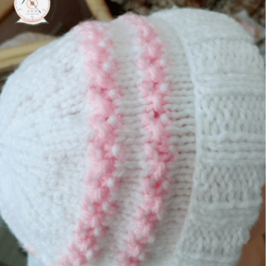 An aran baby hat in pink and white. 10% of all sales goes to breast cancer and honeybee research.