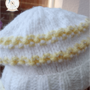 Aran baby hat in lemon and white. 10% of all sales goes to breast cancer and honeybee research.