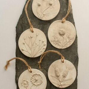 five circular plaster casts with knotted string hangers. Floral casting of wild flowers