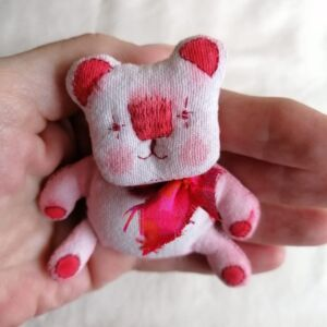 A small pink bear in the palm of a hand