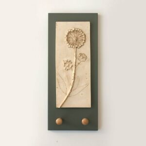 Cast plaster wall plaque of flowering ivy with two shaker wooden pegs on charcoal grey board