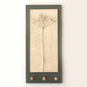 a relief casting in plaster of wild cow parsley on charcoal grey backing board with three shaker wooden pegs