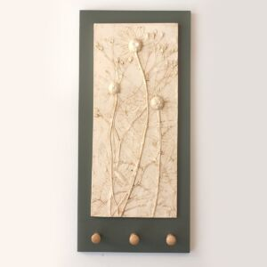 plaster cast of daisy and wild flowers on charcoal grey back board with three shaker wooden pegs