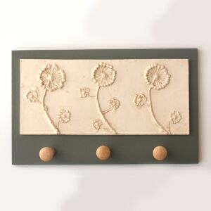 Cast plaster wall plaque of flowering ivy with three shaker wooden pegs charcoal grey board
