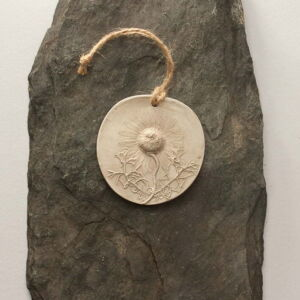 circular plaster cast with knotted string hanger. Floral casting of wild daisy