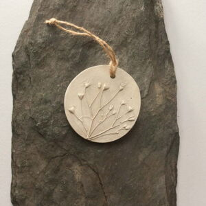 circular plaster cast with knotted string hanger. Floral casting of wild flowers