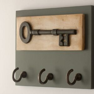 plaster cast of a big key with grey back board and three cast iron hooks