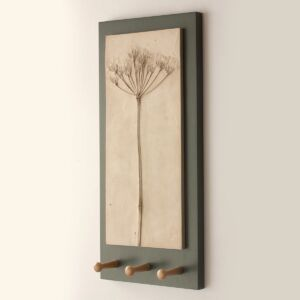 a relief casting in plaster of wild cow parsley on backing board with three shaker wooden pegs