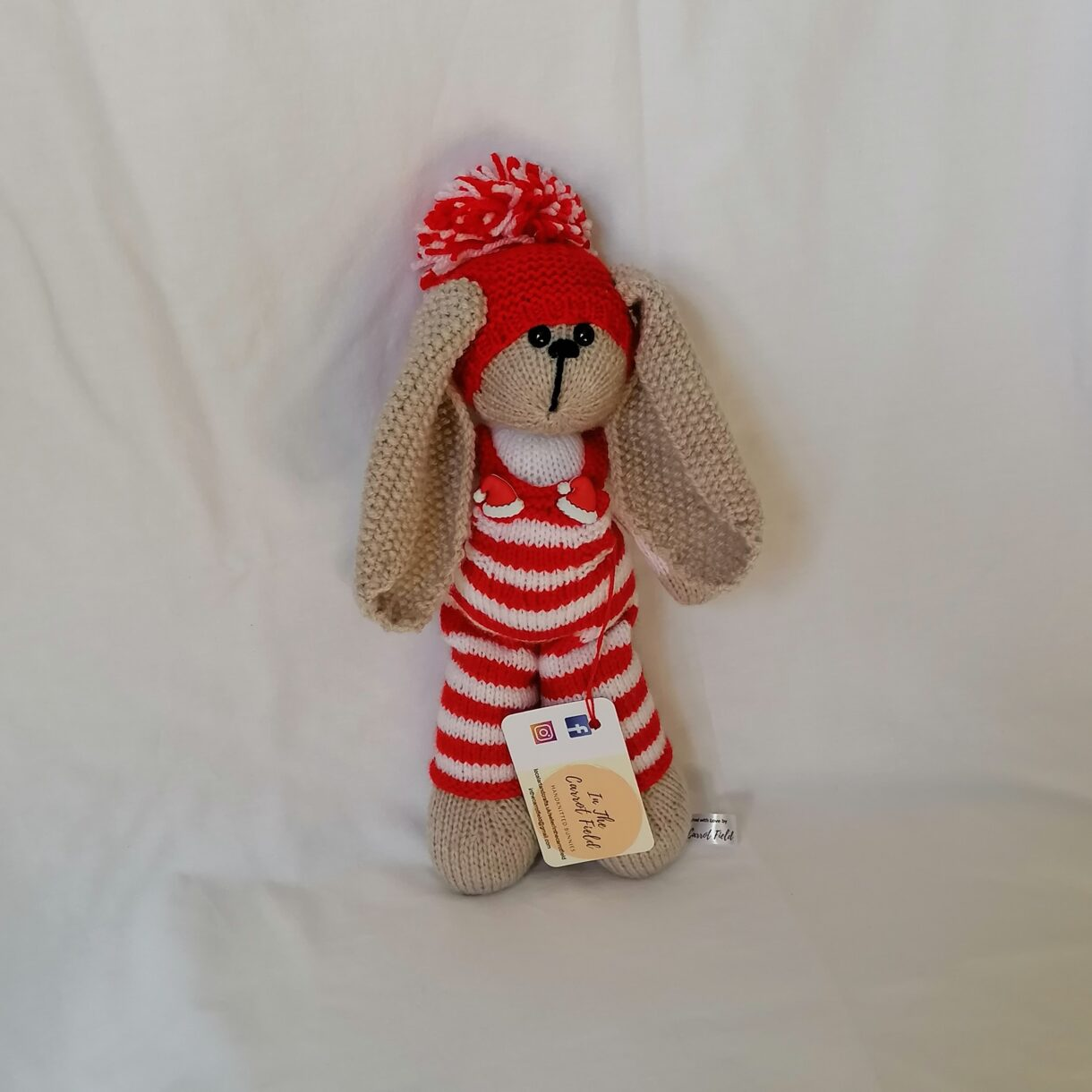 Hand-knitted-soft-toy-Christmas-bunny-red-white-hat-pompom-front